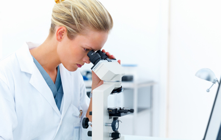 Female researcher looking into a microscope and writing notes at
