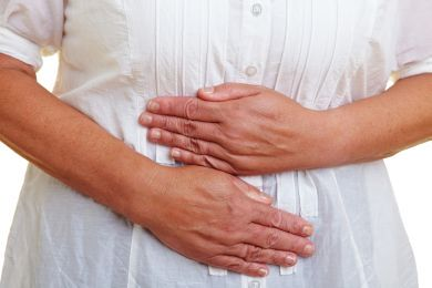 RS5691_sy_woman_holding_hands_to_her_aching_stomach_sh_60644839_clean_2015-lpr